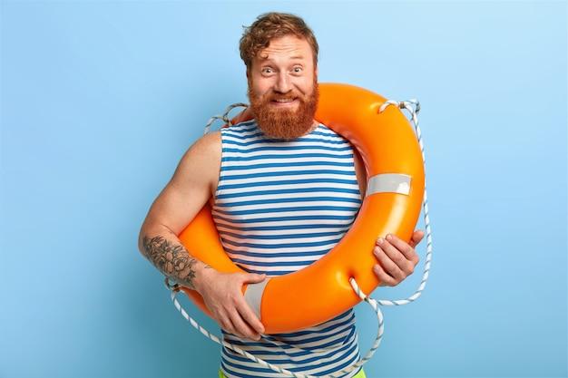 Heureux homme de sauvegarde posant avec bouée de sauvetage