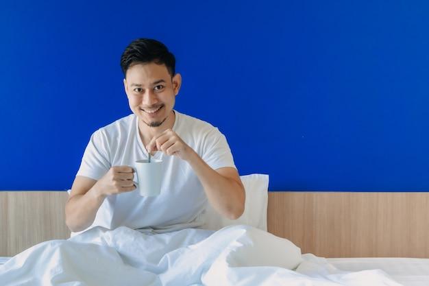 Heureux homme se réveiller sur son lit sur la chambre bleue