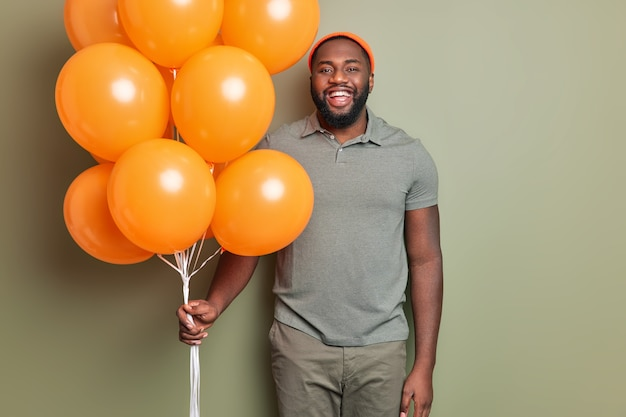 Heureux l'homme se tient heureux vêtu de vêtements décontractés détient bouquet de ballons gonflés orange pose à l'intérieur contre le mur kaki