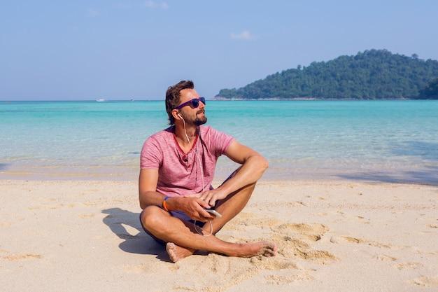 Heureux homme séduisant dans des lunettes de soleil élégantes avec barbe à l'aide de téléphone portable à la plage