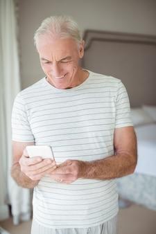 Heureux homme senior à l'aide de téléphone portable dans la chambre