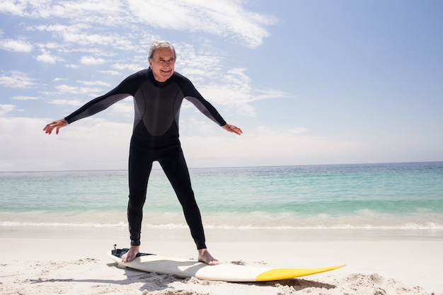 Heureux homme senior en combinaison de natation debout sur la planche de surf