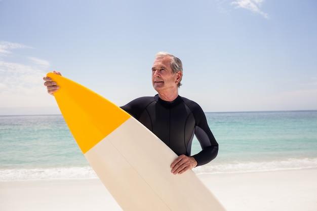 Heureux homme senior en combinaison de surf tenant une planche de surf