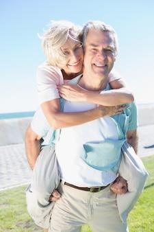 Heureux homme senior donnant sa partenaire un piggy back