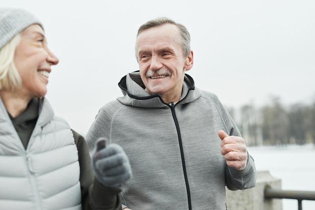 Heureux homme senior avec moustache portant un sweat-shirt gris parlant à sa femme pendant qu'ils courent ensemble le long de la rivière en hiver