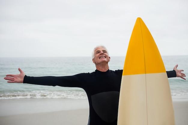 Heureux homme senior avec planche de surf debout sur la plage