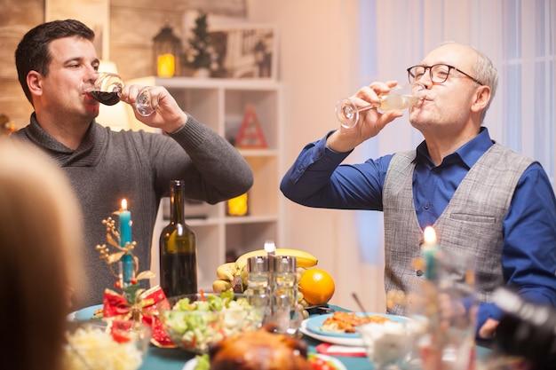 Heureux homme senior et son fils buvant un verre de vin ensemble à la fête de famille de noël.