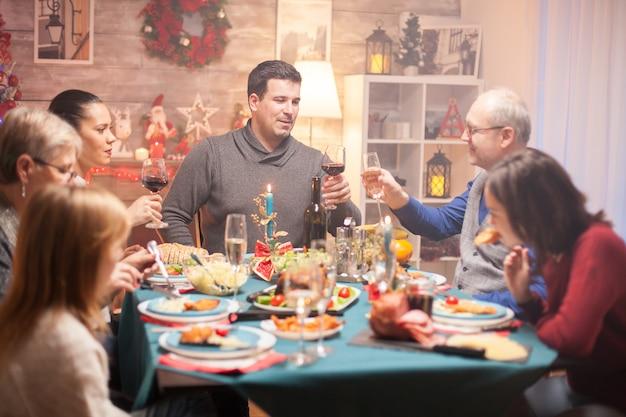 Heureux homme senior et son fils tintant un verre de vin au dîner de noël en famille.