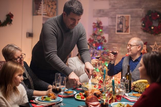 Heureux homme senior tenant un verre de vin et son fils coupant le poulet à la fête de noël.