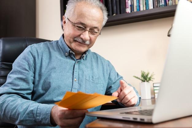 Heureux homme senior travaillant avec un ordinateur portable à la maison, parcourant les factures et les documents. travail à la maison.