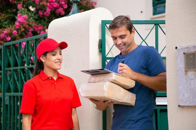 Heureux homme signant une feuille de commande et tenant des boîtes en carton. souriante jolie livreuse debout et en attente de signature du client. service de livraison express et concept d'achat en ligne