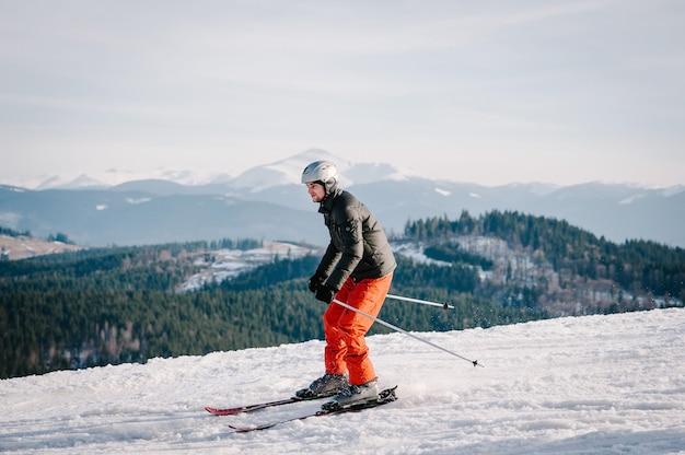 Heureux homme ski dans les montagnes enneigées