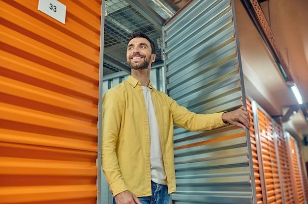 Heureux homme sortant de la porte du conteneur de l'entrepôt
