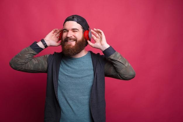 Heureux homme souriant aime écouter de la musique dans des écouteurs sur le rouge.