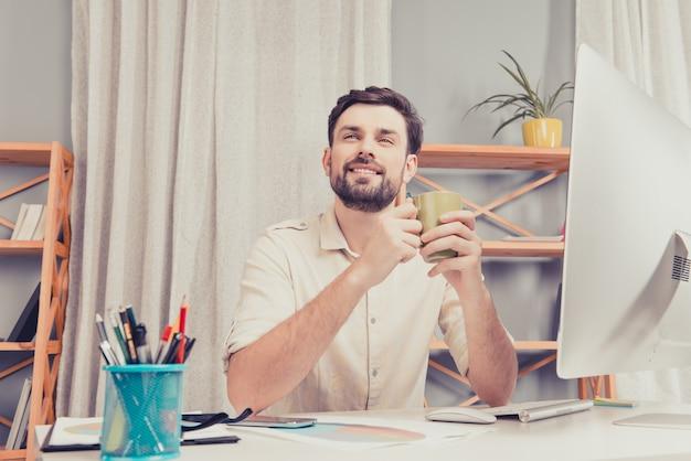 Heureux homme souriant assis à la table et tenant une tasse de café