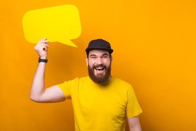 Heureux homme souriant avec barbe en chemise jaune tenant une bulle de dialogue vide vide