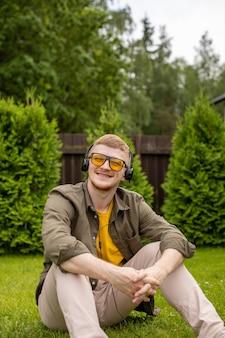 Heureux homme souriant dans les écouteurs écouter de la musique motivante assis sur l'herbe, la nature. liste de lecture de vacances d'été, sons de rêves d'inspiration de voyage de liberté, concept gagnant. copier l'espace de texte