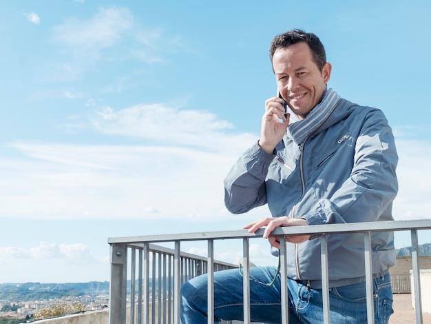 Heureux homme souriant, parlant au téléphone tout en restant à l'extérieur