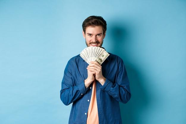 Heureux homme souriant tenant de l'argent et regardant la caméra pensif, pensant faire du shopping, debout sur fond bleu.