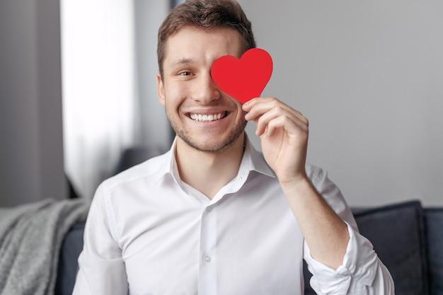 Heureux homme souriant et tenant coeur de papier