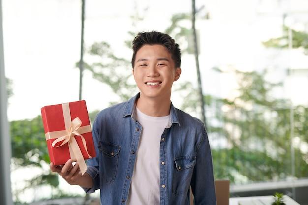 Heureux homme souriant tout en montrant une boîte-cadeau