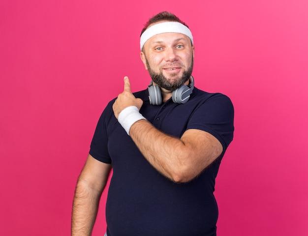 Heureux homme sportif slave adulte avec des écouteurs portant un bandeau et des bracelets pointant derrière isolé sur un mur rose avec copie espace