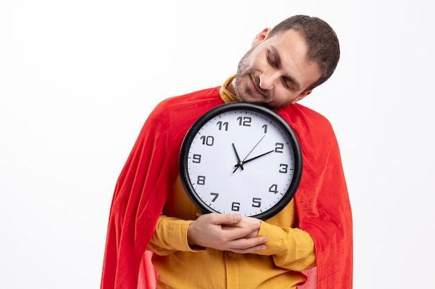 Heureux homme de super-héros avec manteau rouge tient horloge isolé sur mur blanc