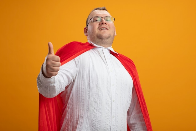 Heureux homme de super-héros slaves adultes en cape rouge portant des lunettes montrant le pouce vers le haut en regardant la caméra isolée sur fond orange avec copie espace