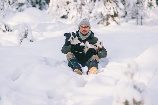 Heureux homme tenant un beau chien dans ses mains dans la forêt enneigée.