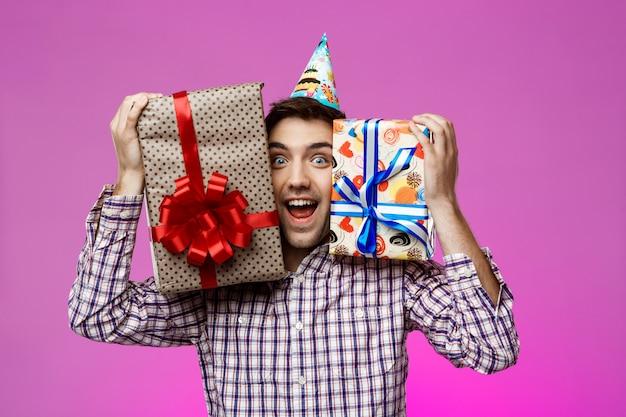 Heureux homme tenant des cadeaux d'anniversaire dans des boîtes sur le mur violet.