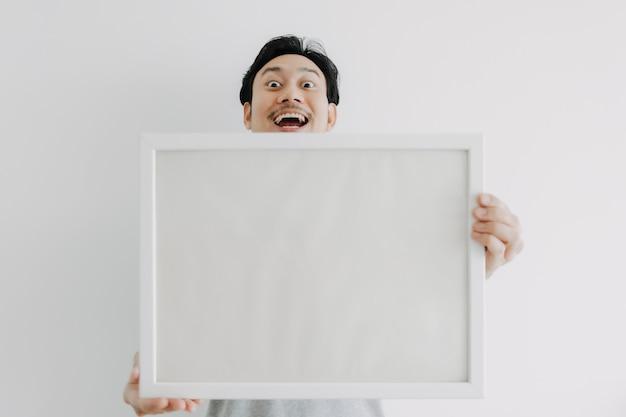 Heureux homme tenant un cadre photo vide isolé sur fond blanc
