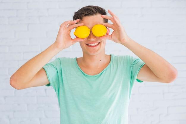 Heureux homme tenant des citrons entiers devant ses yeux