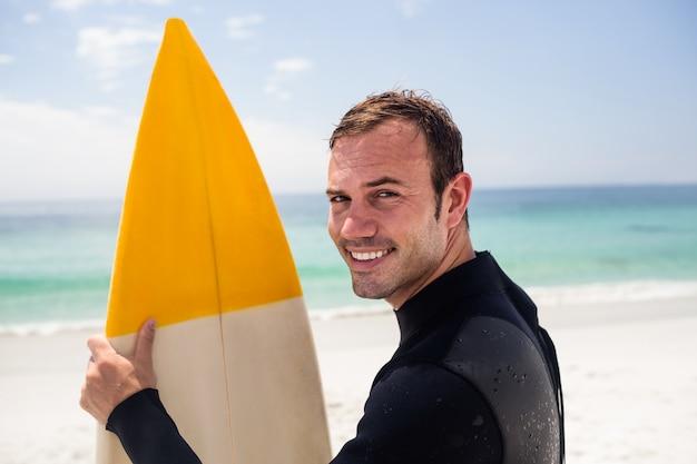 Heureux homme tenant une planche de surf sur la plage