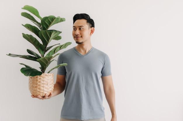 Heureux homme tenant une plante d'intérieur isolé sur fond blanc
