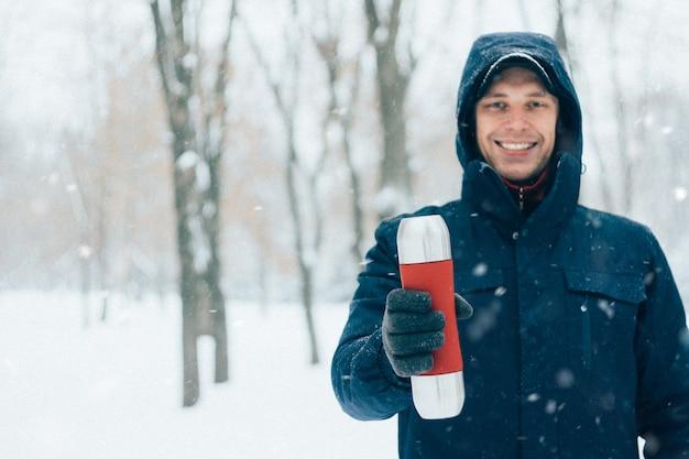 Heureux homme tenant un thermos à winter park avec de la neige
