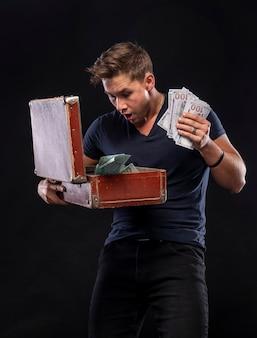 Heureux homme tenant une valise pleine d'argent isolé sur fond noir