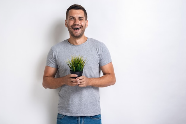 Heureux homme tient un pot d'herbe fraîche dans ses mainsconcept journée mondiale de l'environnement