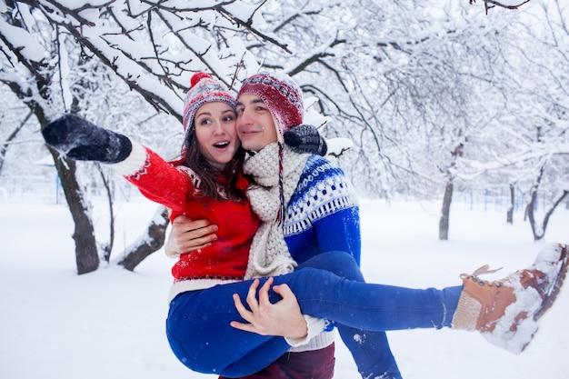 Heureux homme tient sa petite amie dans ses bras en forêt d'hiver