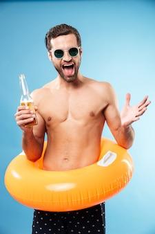 Heureux homme torse nu souriant portant un anneau gonflable