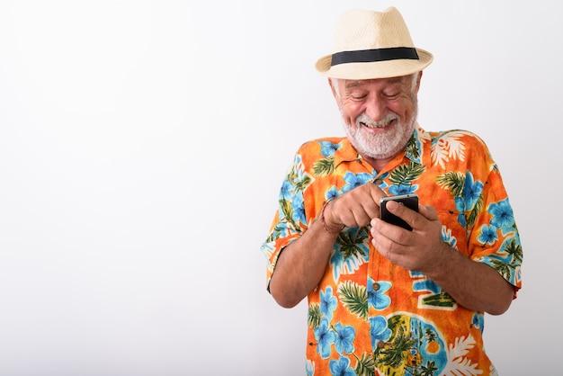 Heureux homme de touriste barbu senior souriant et gloussant tout en utilisant un téléphone mobile sur blanc