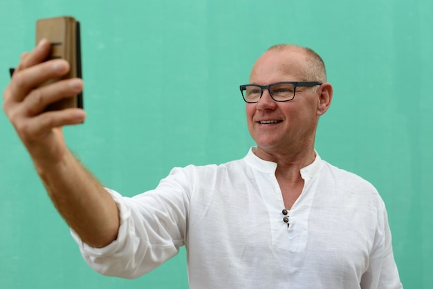 Heureux homme touriste beau mature prenant selfie contre le mur vert à l'extérieur
