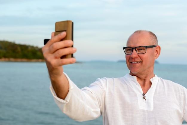 Heureux homme touriste beau mature prenant selfie contre vue sur la plage en plein air