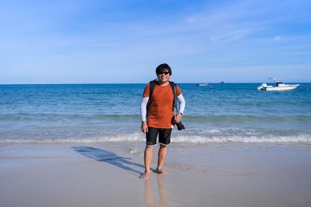 Heureux homme touristique asiatique sac à dos d'âge moyen debout sur la plage et le sourire, homme avec appareil photo se détendre en vacances sur la plage de la mer bleue ondulée