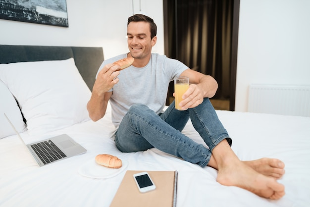 Heureux homme travaillant et prenant son petit déjeuner au lit