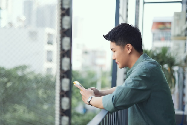 Heureux homme utilisant un téléphone portable au balcon