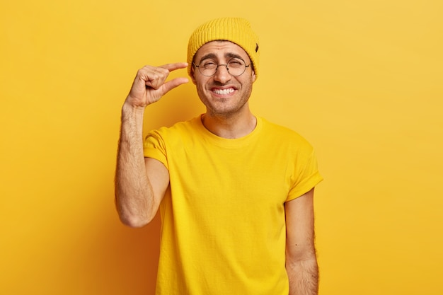 Heureux homme en vêtements jaunes décontractés, fait un petit geste, montre quelque chose de très peu, sourit joyeusement, a une expression joyeuse, porte des lunettes transparentes