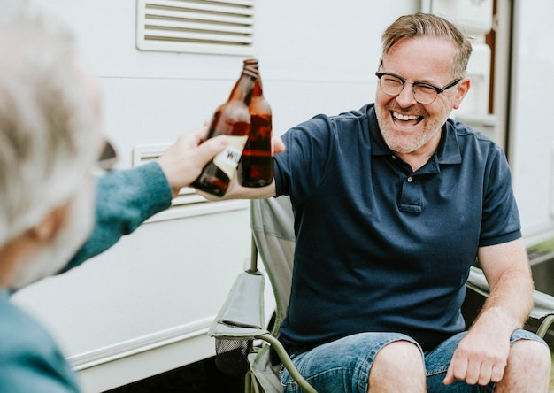 Heureux hommes âgés tintant des bouteilles de bière