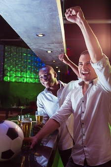Heureux hommes regardant un match de football au bar