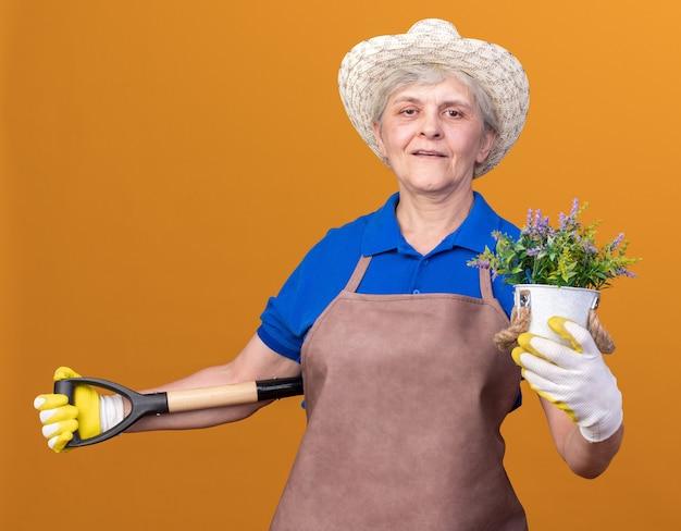 Heureux jardinier femme âgée portant un chapeau et des gants de jardinage tenant un pot de fleurs et une pelle derrière le dos