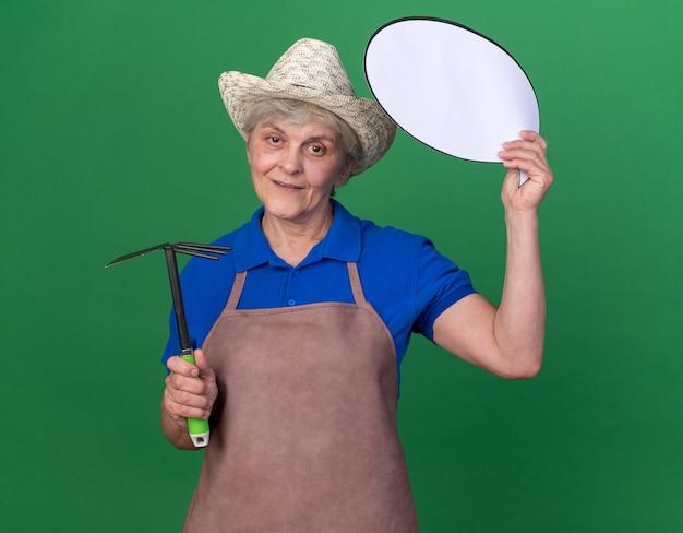 Heureux jardinier femme âgée portant un chapeau de jardinage tenant un râteau et une bulle de dialogue